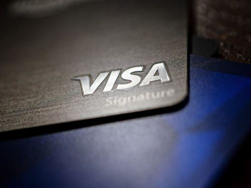 A Visa Inc. credit card is arranged for a photograph in Tiskilwa, Illinois, U.S., on Tuesday, Sept. 18, 2018. Visa and Mastercard agreed to pay as much as $6.2 billion to end a long-running price-fixing case brought by merchants over card fees, the largest-ever class action settlement of an antitrust case. Photographer: Daniel Acker/Bloomberg