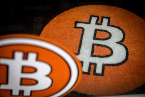 A bitcoin logo on the carpet of a bitcoin automated teller machine (ATM) kiosk in Barcelona, Spain, on Tuesday, Feb. 23, 2021. Bitcoin climbed, aided by supportive comments from Ark Investment Management's Cathie Wood and news that Square Inc. boosted its stake in the cryptocurrency. Photographer: Angel Garcia/Bloomberg