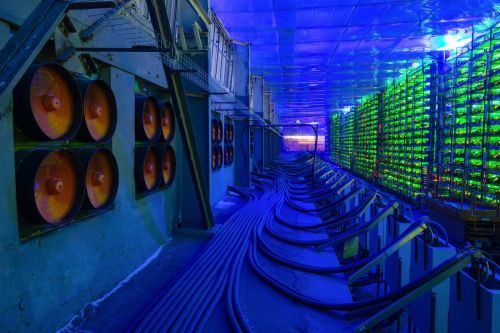 Industrial cooling fans operate to thermally regulate illuminated mining rigs at the CryptoUniverse cryptocurrency mining farm in Nadvoitsy, Russia, on Thursday, March 18, 2021. The rise of Bitcoin and other cryptocurrencies has prompted the greatest push yet among central banks to develop their own digital currencies. Photographer: Andrey Rudakov/Bloomberg